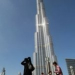 "An Emirati woman and her children walk past Burj Khalifa, the world's tallest tower, in debt-ridden Dubai. Dubai's embattled group Dubai World, whose default fears had rocked global markets, Thursday said it reached agreement ""in principle"" with most of its bank lenders to restructure some 23.5 billion dollars in debt."