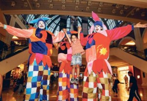 *  Eliyah Saifan getting carried away by stilt walkers at the Mall of the Emirates as part of DSS festivities     * Image Credit: HADRIAN HERNANDEZ/Gulf News