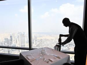 "Bar captain, Solomon from Kenya, places a bottle of champagne at ""At.mosphere"" the world's highest restaurant in the Burj Khalifa in Dubai"