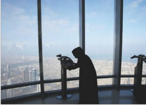 A woman peers through binoculars from the observation deck on the 124th floor of the Burj Khalifa Tower. Photograph by: Ahmed Jadallah, Reuters, File, Edmonton Journal